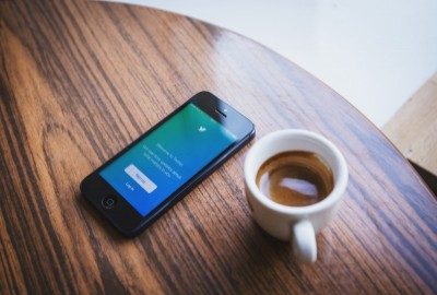 Twitter en un movil sobre una mesa y un cafe